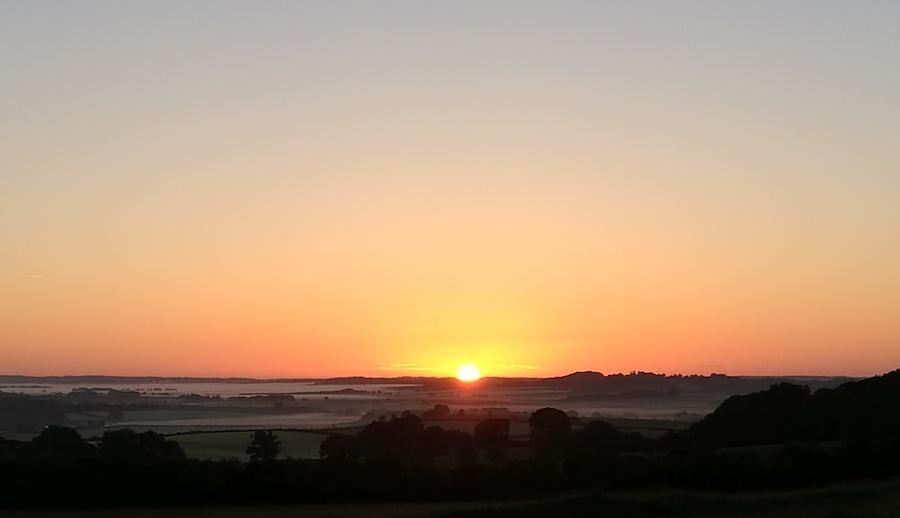 Sun rising on summer solstice 2019 at Badbury Rings